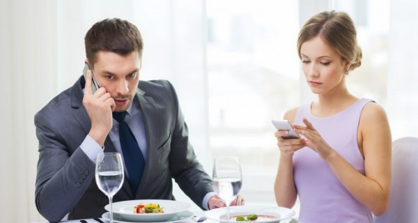 Couple-on-cell-phones-during-date-750x400