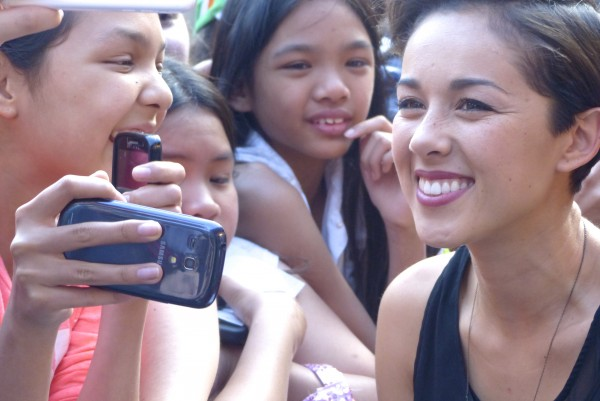 Kina Grannis taking photos with fans on the red carpet