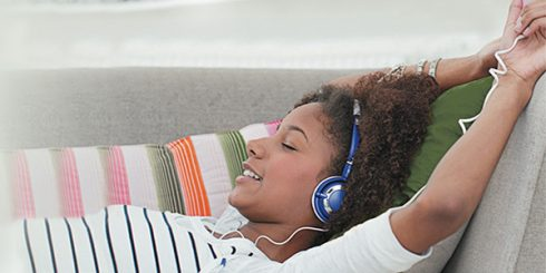 Girl relaxing on couch with headphones music