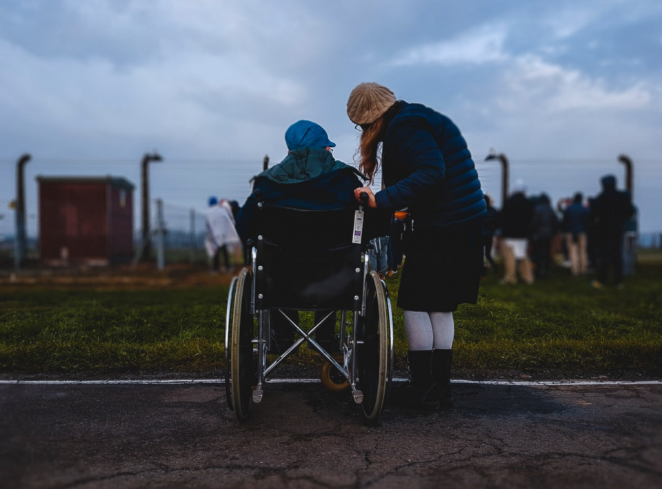 Person sitting in wheelchair with person standing beside them