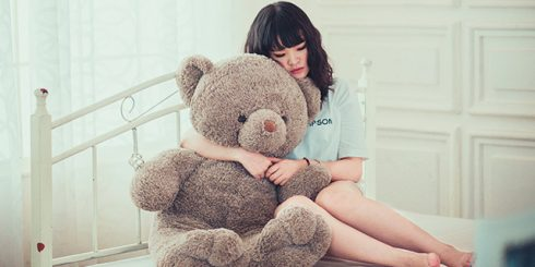 sad depressed hugging teddy bear in isolation