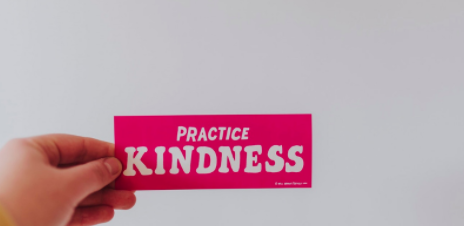 a hand holds a card that reads practice kindness