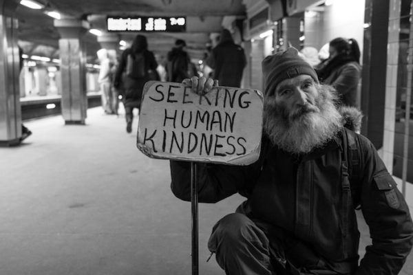 Bearded Man holds up cardboard sign Seeking Human Kindness