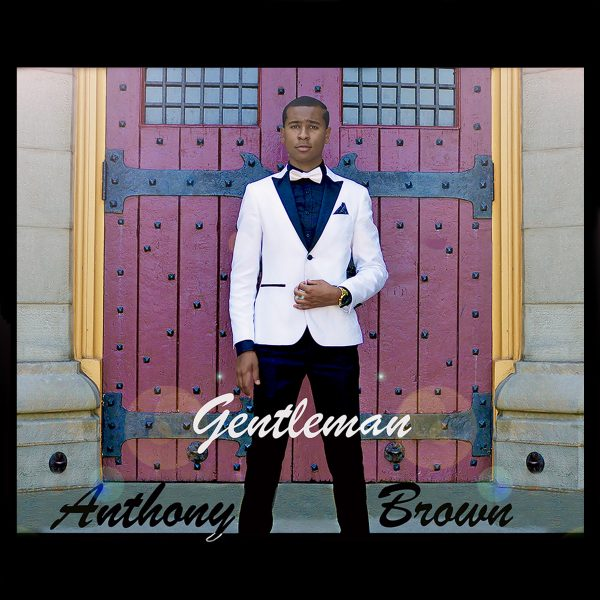 Anthony Brown wears formal white jacket and stands in front of gothic red door